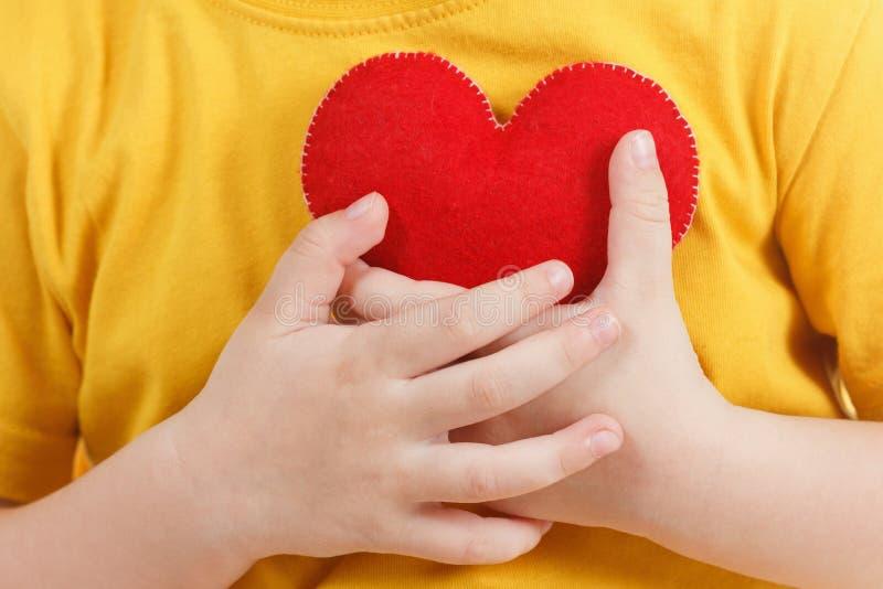 拿着一个红色心脏小雕象的微笑的男孩 爱,家庭的标志, 家庭和孩子的概念 免版税库存图片