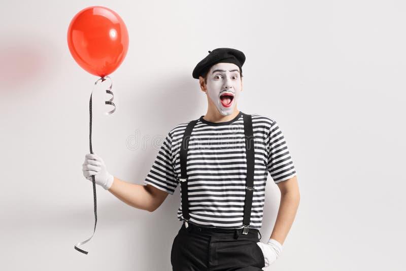 拿着一个红色气球和倾斜对墙壁的笑剧 图库摄影