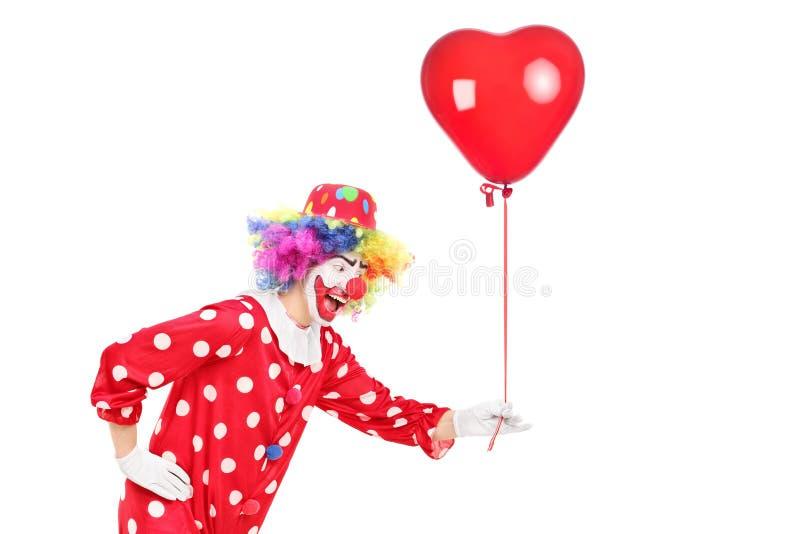 拿着一个红色气球的男性小丑 免版税库存照片