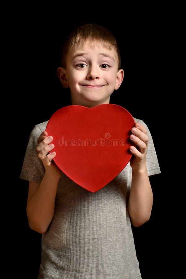 拿着一个红色箱子的白肤金发的男孩以在黑背景的心脏的形式 爱和家庭观念 垂直的框架 库存照片