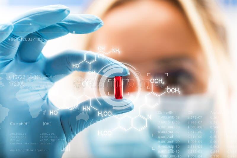 拿着一个红色透明药片的年轻可爱的女性科学家 库存图片