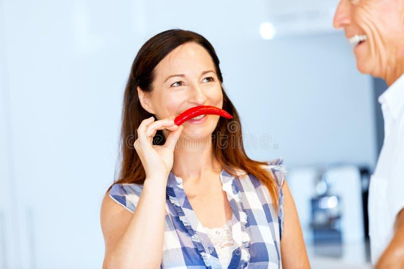 拿着一个红辣椒的妇女在她的面孔旁边 图库摄影