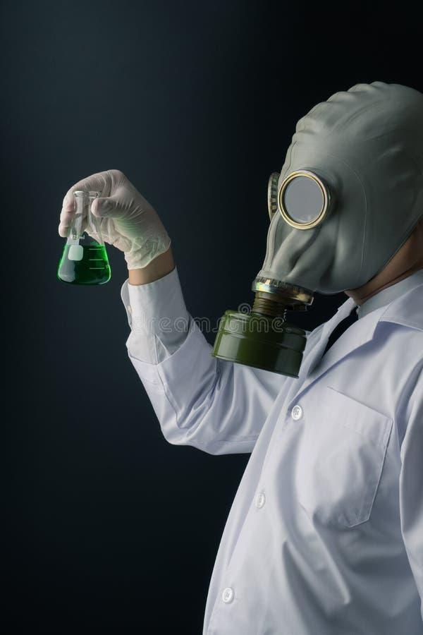 拿着一个绿色毒性化学物质烧瓶的防毒面具的一位可怕科学家 库存图片