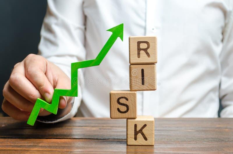 拿着一个绿色箭头的商人在词风险附近 改进企业韧性,减少风险和费用 ?? 库存图片
