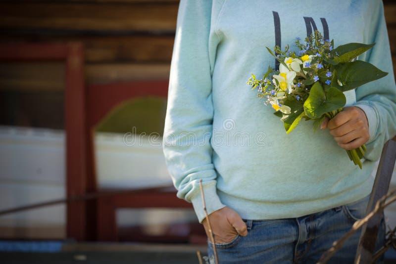拿着一个美丽的庭院的少妇在她的手上开花 夏天花束在女孩` s手上 室外 免版税库存图片