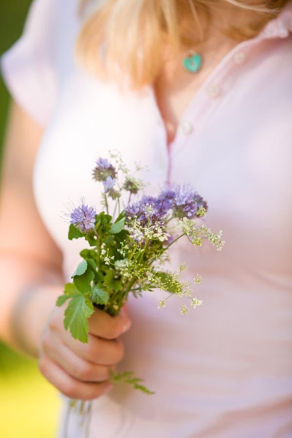 拿着一个美丽的庭院的桃红色的年轻白肤金发的妇女在她的手上开花 夏天花束在女孩` s手上 库存图片