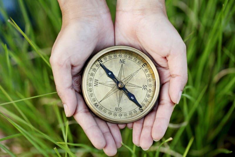 拿着一个老指南针的手 免版税库存照片