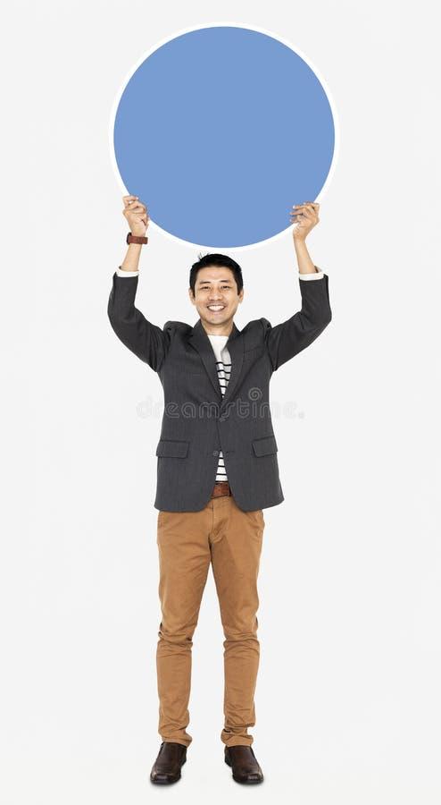 拿着一个蓝色圆的委员会的商人 图库摄影