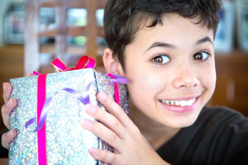 拿着一个被包裹的圣诞节礼物的年轻男孩 库存图片