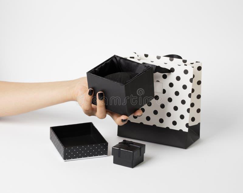 拿着一个被打开的,空的礼物盒的女性手 另一个关闭框,下面礼物袋子 免版税库存照片