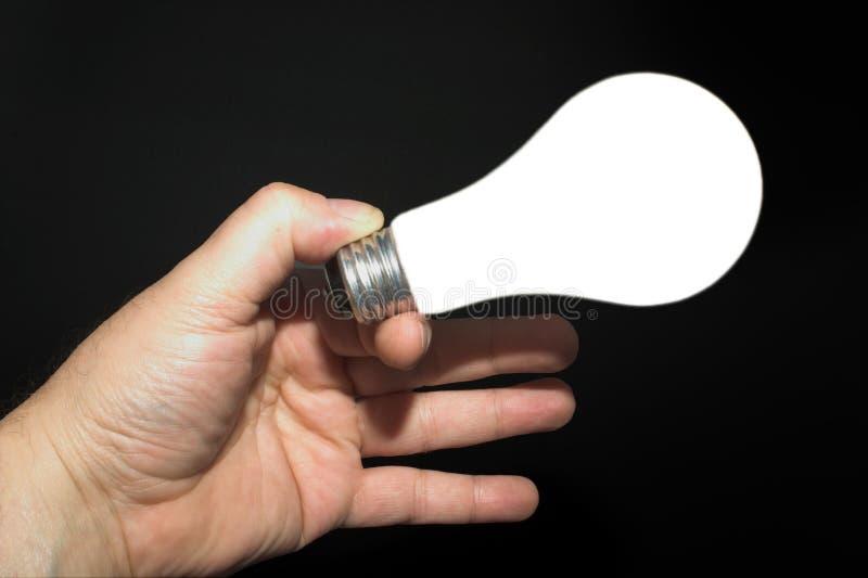 拿着一个被点燃的电灯泡的现有量 免版税库存照片