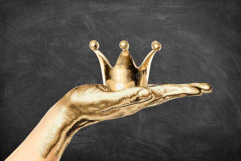 拿着一个金黄冠有黑暗的黑板背景的被镀金的女性手 皇族、succes和优质概念 免版税库存图片