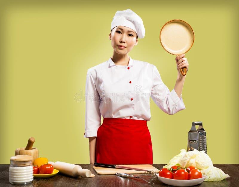 拿着一个陶瓷平底锅的中国妇女主厨 库存照片