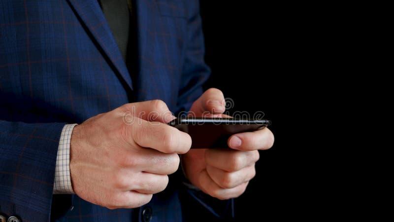 拿着一个黑智能手机特写镜头的男性手 手指接触电话的触摸屏幕,当键入时 ?? 免版税库存照片