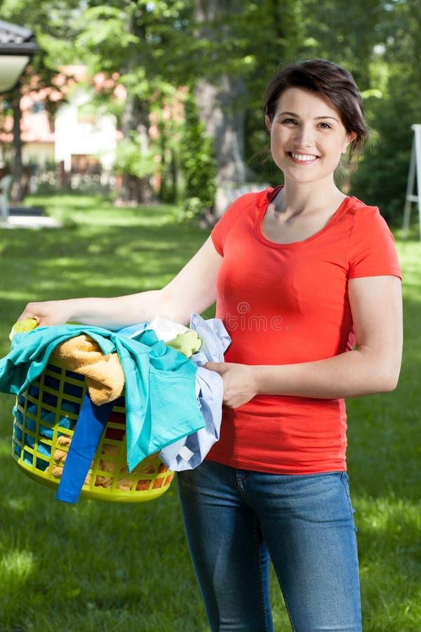 拿着一个洗衣篮的妇女在庭院里 免版税库存图片