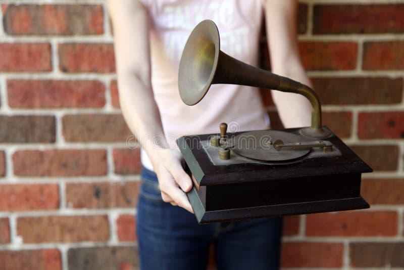 拿着一件传统gramaphone复制品的妇女 图库摄影
