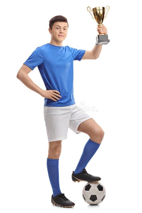 拿着一件金黄战利品的少年足球运动员 库存照片