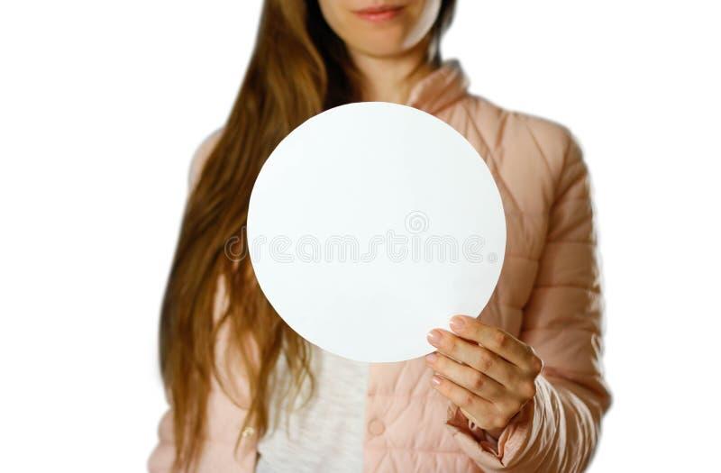 拿着一份圆的白色传单的一件温暖的冬天夹克的一名妇女 白纸 关闭 背景查出的白色 图库摄影