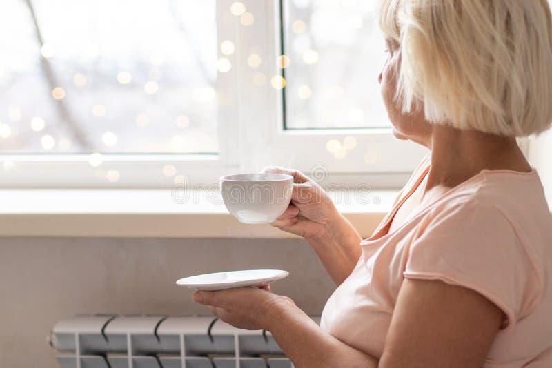 拿着一份热的咖啡的妇女手 免版税库存照片