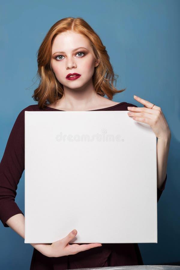 拿着一副白色空白的横幅的一个少妇的画象 免版税库存图片