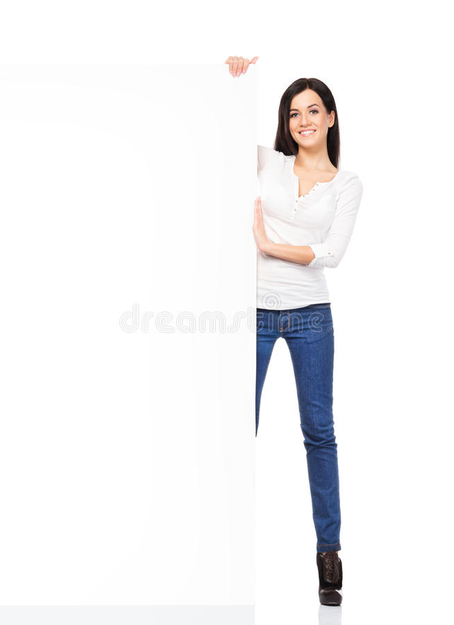 拿着一副空白的横幅的牛仔布牛仔裤的年轻性感的妇女 库存照片