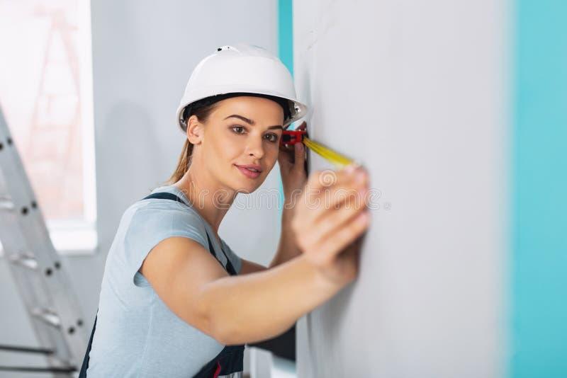 拿着一卷测量的磁带的严肃的女性建造者 免版税库存图片