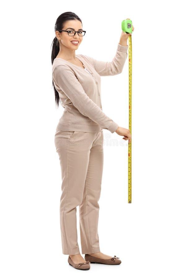 拿着一卷测量的磁带的女孩 免版税库存图片