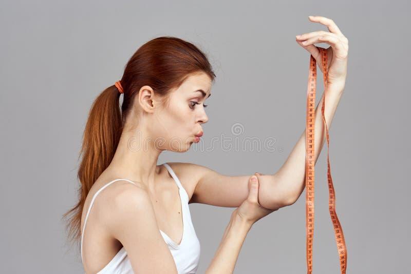拿着一卷测量的磁带,饮食的妇女 免版税库存照片