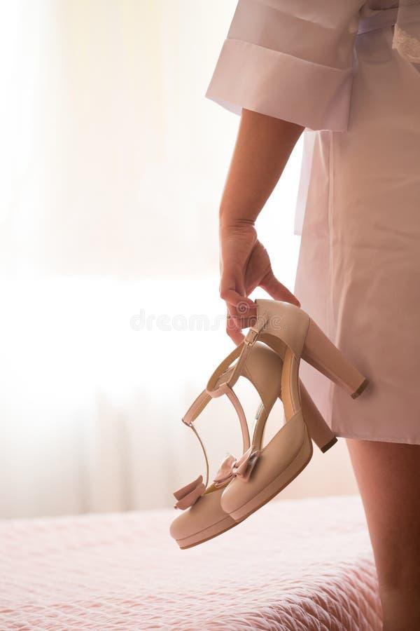 拿着一双鞋的妇女 免版税库存照片