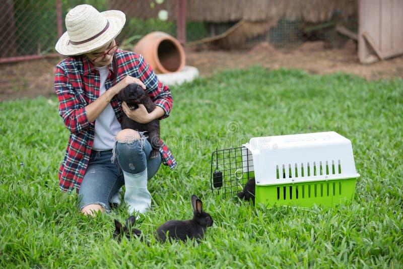拿着一只兔子的女孩农夫在兔子农场 免版税库存图片