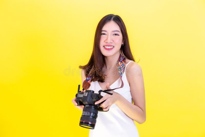 拿着一台专业照相机和拍在黄色背景的可爱的亚裔妇女照片 免版税库存图片