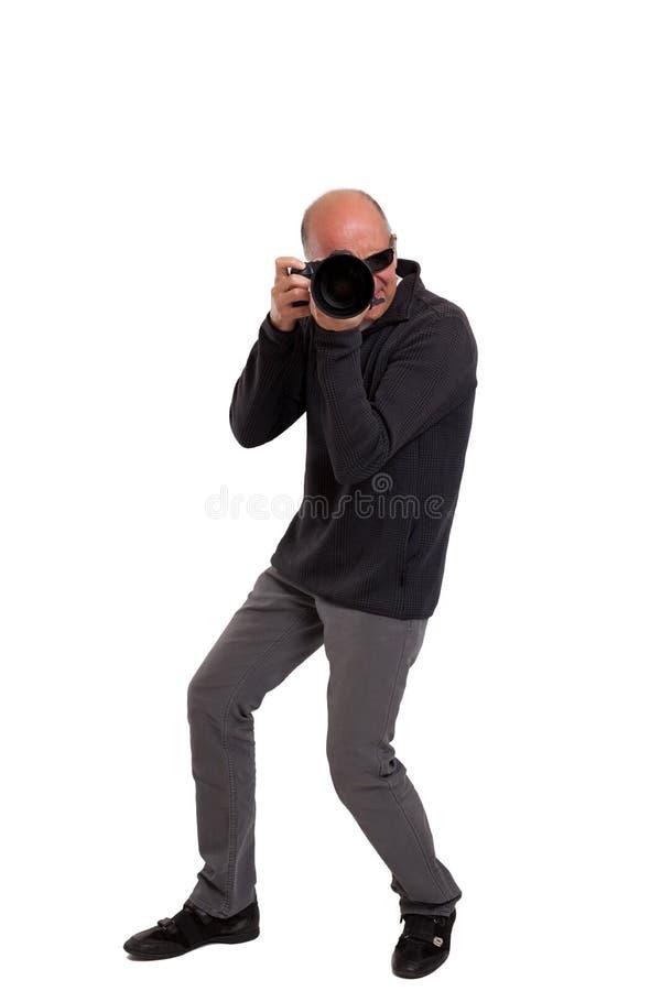 拿着一台专业照相机的摄影师 免版税库存图片