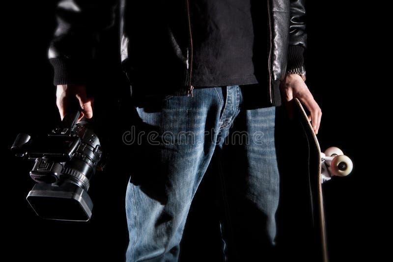 拿着一台摄象机和滑板的溜冰板者 库存照片
