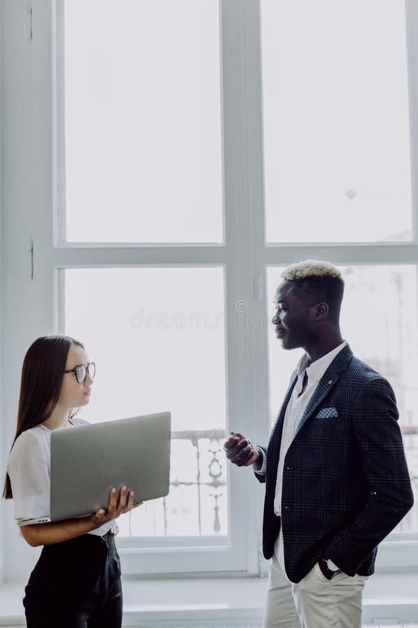 拿着一台膝上型计算机在办公室窗口前面的小组商人、非洲的男人衣服的和亚裔妇女在背景 库存照片