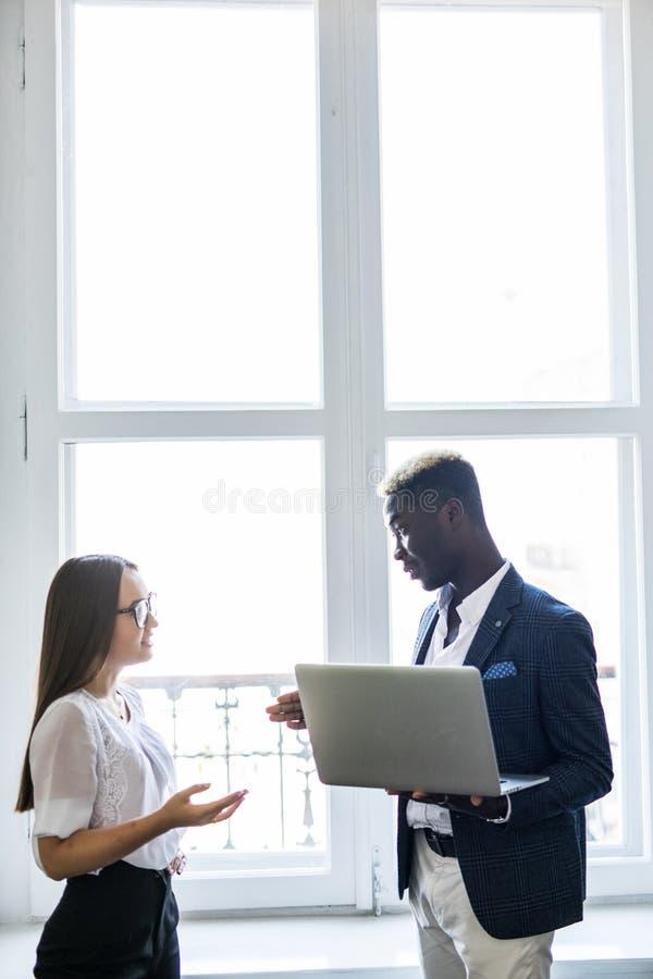 拿着一台膝上型计算机在办公室窗口前面的小组商人、非洲的男人衣服的和亚裔妇女在背景 库存图片
