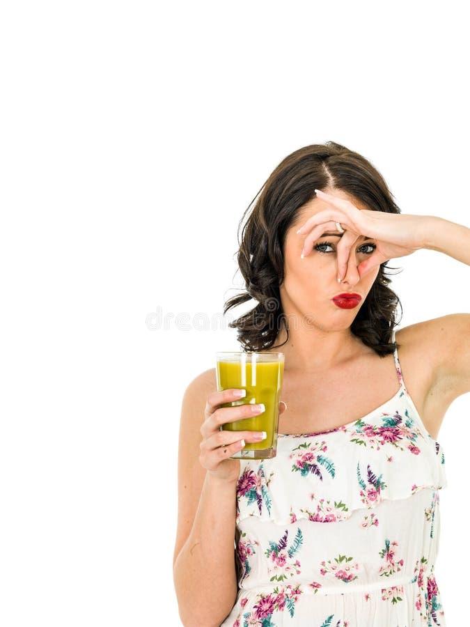 拿着一名新鲜水果圆滑的人的一杯的妇女显示她的Disl 图库摄影