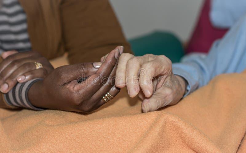拿着一名资深妇女的护士的手 帮手的概念,老人的关心 库存图片