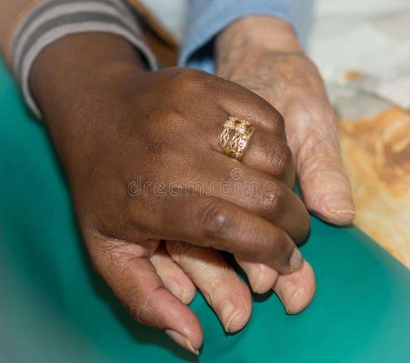 拿着一名资深妇女的护士的手 帮手的概念,老人的关心 免版税库存图片