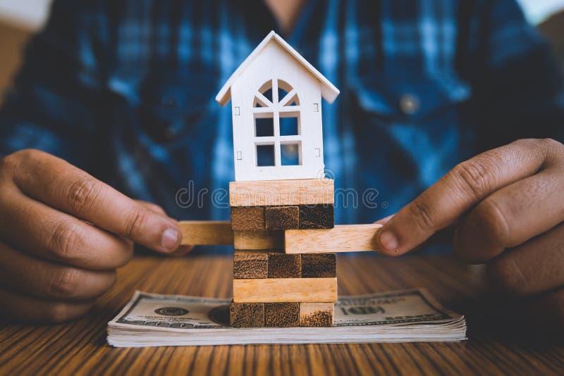拿着一块木头与式样白色房子的块的手美元钞票的 保险和物产投资不动产concep 免版税库存照片
