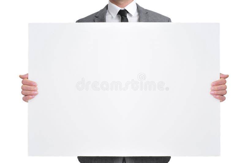 拿着一块空白的牌的衣服的人 免版税图库摄影
