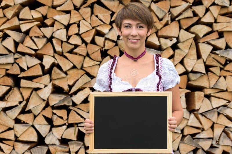 拿着一块空白石板的少女装的少妇 免版税库存图片