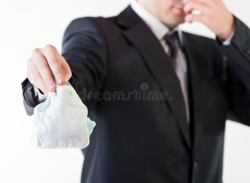 拿着一块肮脏的尿布的商人 免版税图库摄影