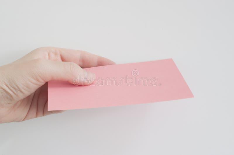 拿着一张桃红色纸的女商人的手 免版税图库摄影