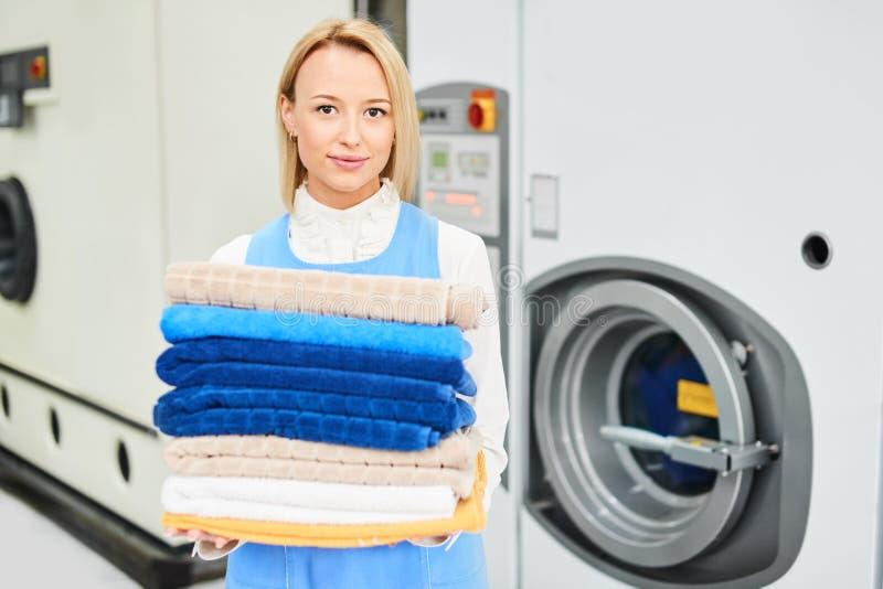 拿着一张清洁毛巾的女孩洗衣店工作者的画象 免版税库存图片