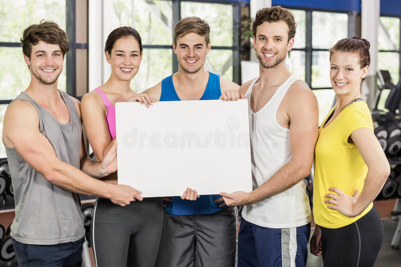 拿着一张白色卡片的健身类 免版税库存照片
