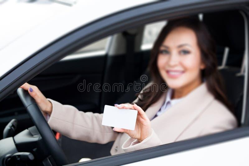 拿着一张白色空白的名片的妇女司机 库存图片