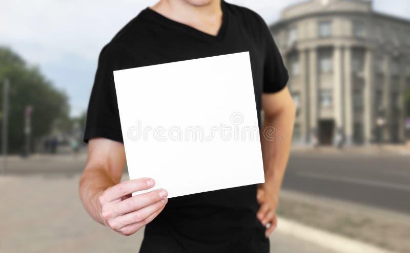 拿着一张白色纸片的一个人 拿着小册子 ?? 城市的背景 免版税图库摄影