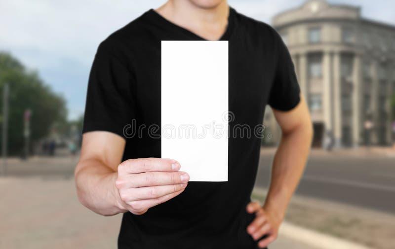 拿着一张白色纸片的一个人 拿着小册子 ?? 城市的背景 库存照片