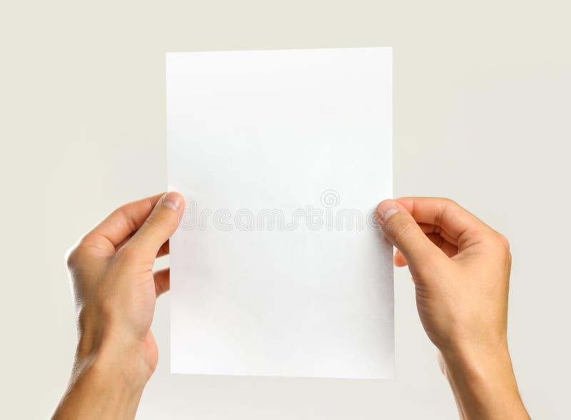拿着一张白色纸片的男性手 隔绝在灰色背景 免版税图库摄影