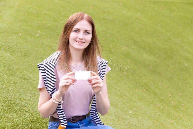 拿着一张空白名片的年轻微笑女 免版税库存图片